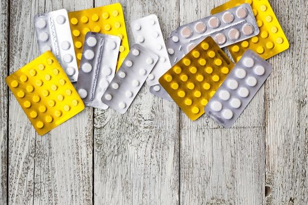 薬のパックの錠剤。ブリスターパックの丸薬、カプセル、錠剤は白い木製のテーブルの水疱に詰め