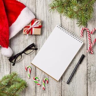 コピースペース付きのクリスマスアイテムとビジネスアイテムは、サンタキャップメモ帳ペンメガネと装飾されたギフトボックスとモミの木をトリミング
