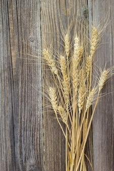 自然の古い木製のテーブルに小麦の穂