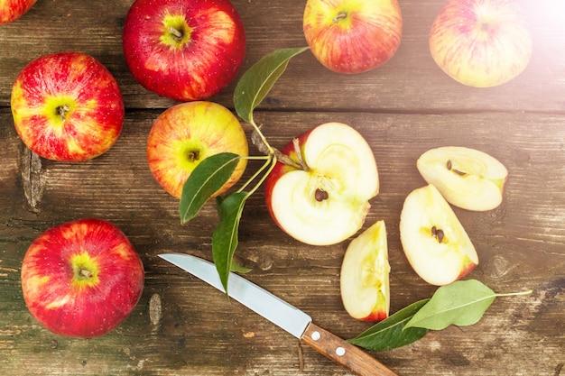 Красное яблоко нарезанное и нож на старый деревянный стол