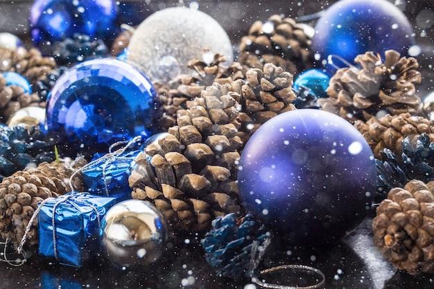 Рождественские фон с синими серебряными шариками и шишка.