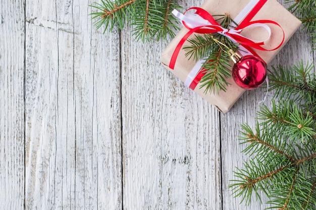 Новогодний фон с украшениями и подарочные коробки на белой деревянной доске