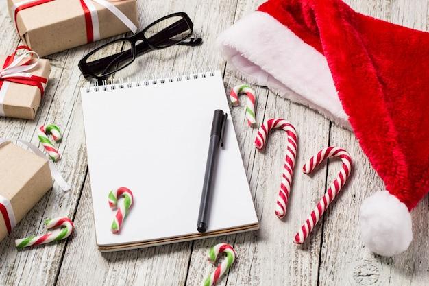 コピースペース付きのクリスマスアイテムと新年アイテムサンタキャップメモ帳ペングラスと装飾ギフトボックス