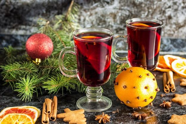 クリスマスホットワイン、ジンジャービスケットオレンジシナモンクローブアニス、暗いテーブルの上のモミの木