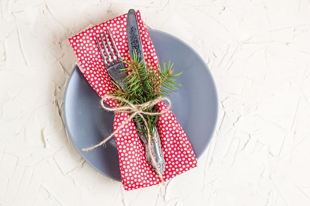 白いテーブルにフォークナイフナプキンとモミの木のブランチとクリスマスメニューの背景。コピースペース、トップビュー