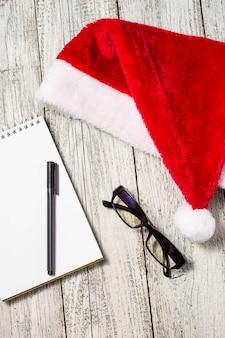 赤いサンタ帽子、メガネ、メモ帳、あなたの願いのためのペンでクリスマスと新年の背景