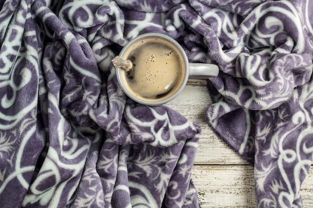 木製のテーブルと暖かい格子縞のコーヒーカップ。秋または冬のコンセプト