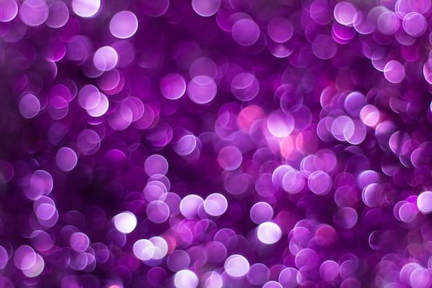 紫の光沢のあるキラキラ休日美しい抽象的なボケ背景のぼかし