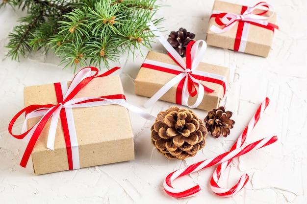 Новогоднее украшение с шишками, еловыми ветками, подарочными коробками и леденцами