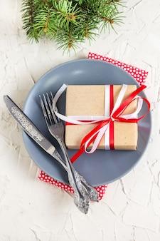 白いテーブルの上の皿にギフトとクリスマステーブルの設定。クリスマスコンセプトトップビュー