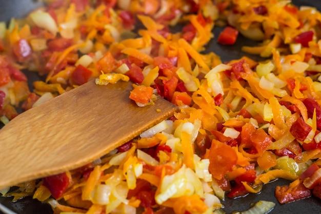 フライパンでひまわり油で玉ねぎ、ニンジン、パプリカ、トマト、ハーブ、スパイスのスープのローストを調理する