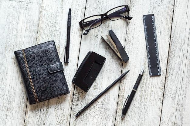 黒と白の静物:開いた空白のメモ帳、ノート、ペン、鉛筆、眼鏡、財布。