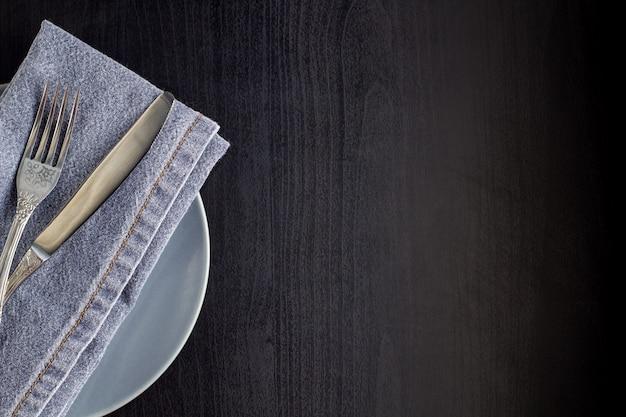 Сервировка стола с пустой тарелкой салфеткой вилкой и ножом на черном фоне