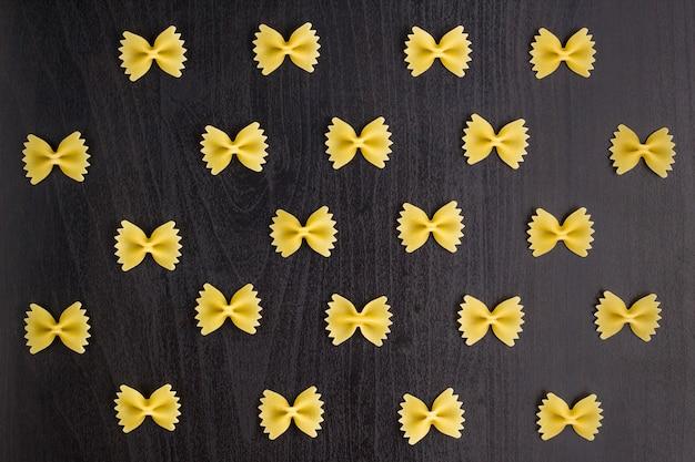 黒の背景にファルファッレパスタの山のパターン