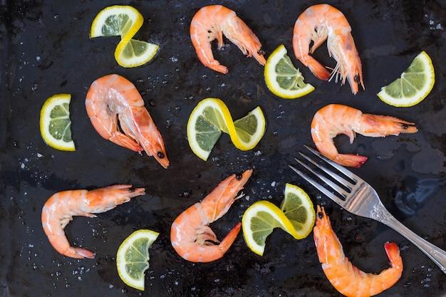 エビ、レモン、海の塩、濃い黒のテーブルにフォーク