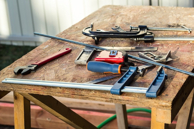 ペンチ、パイプレンチ、ドライバー、クランプ、ルーレットの古い木製テーブルの構築ツールの構成