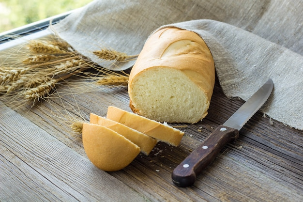 木製のテーブルのクローズアップに小麦のスパイクとパンをスライス