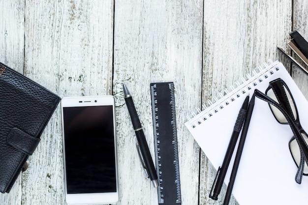 黒と白の静物:空白のメモ帳、ノート、ペン、鉛筆、眼鏡、財布を開けた。