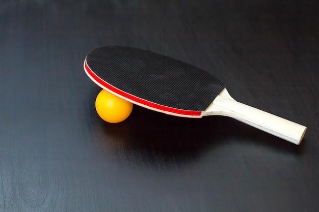 卓球または卓球ラケットと黒いテーブルの上のボール