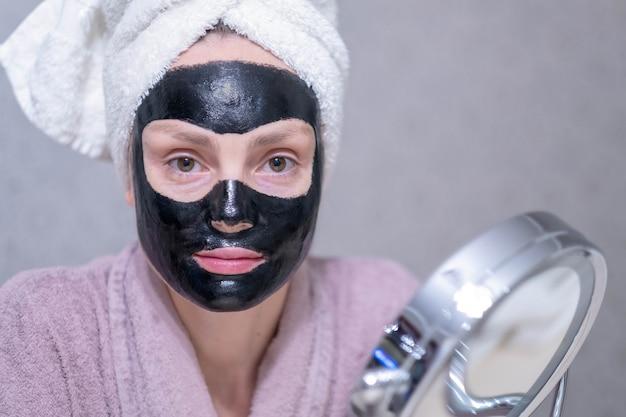 Молодая девушка в очищающей черной угольной маске на лице.