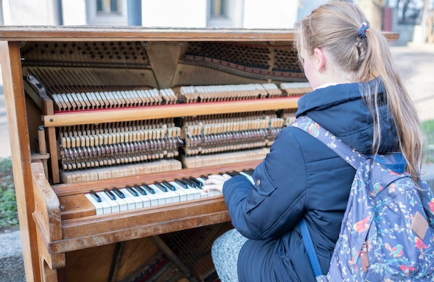 路上で女の子が古いピアノを弾きます。