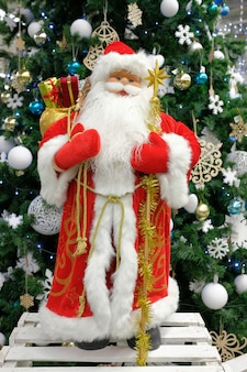 完全な成長のクリスマス装飾サンタクロースは、クリスマスツリーの背景に立っています。クリスマスの組成