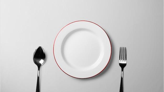 白いテーブルの上のスプーンとフォークのプレート_孤立した背景ストック写真