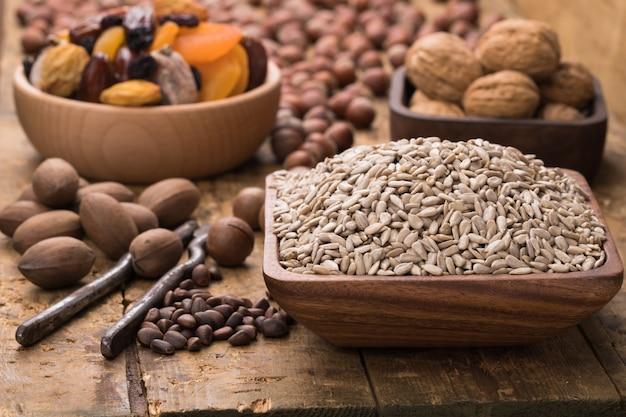 Семена подсолнуха очищенные в деревянной миске на столе, стиль гранж.