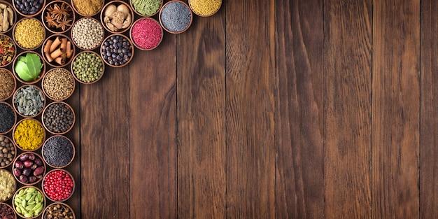 インドのスパイスとハーブの木製のテーブル。空スペースの調味料コレクション
