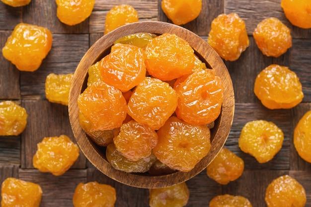砂糖漬けのフルーツ、木製のボウル、トップビューでパラダイスアップル。