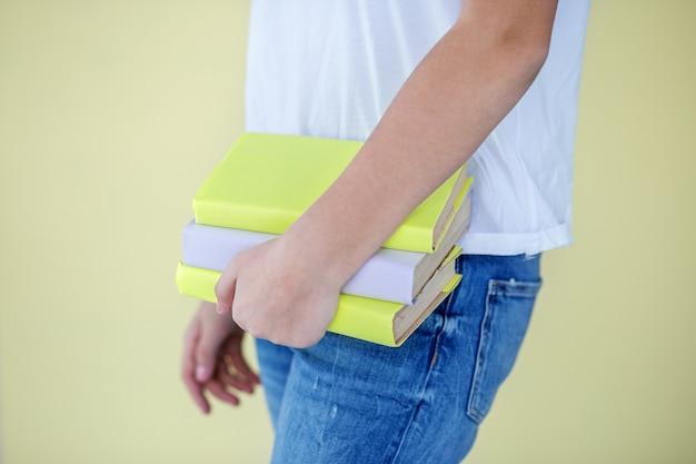子供の手の中にたくさんの本があります。学校に戻る。