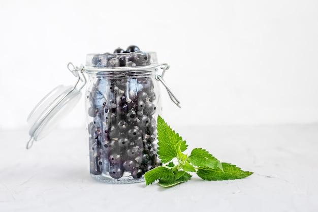ガラス瓶の中のミントとおいしい黒スグリ。白色の背景。
