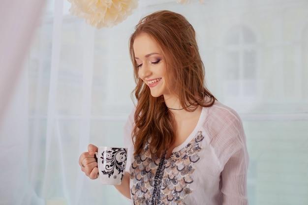 Девушка смеется и пить кофе.