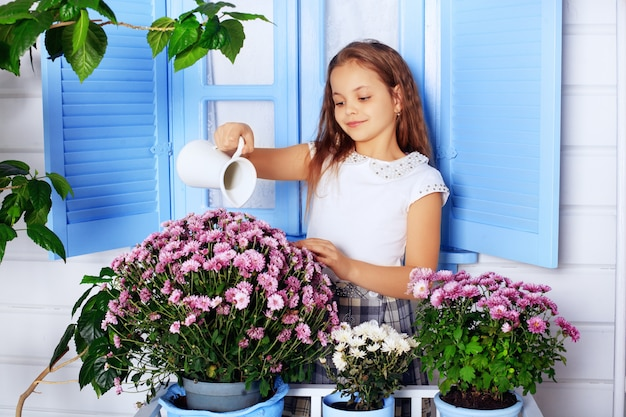 花に水をまく美しい巻き毛の小さな女の子。