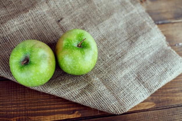 Две сочные зеленые яблоки на столе. концепция диеты