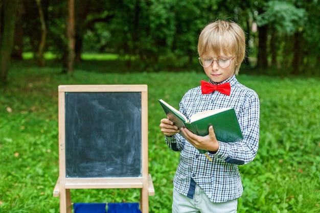 ノートブックとメガネでスタイリッシュな金髪の小さな男の子。学校のコンセプトに戻る
