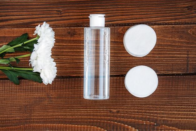 木製の背景に強壮剤と化粧品の綿パッド。コンセプト