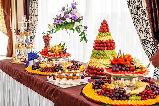 フルーツとケーキのあるエレガントなテーブル。パーティー、食べ物の概念