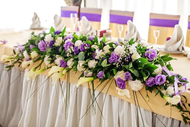 テーブルの上のフラワーアレンジメント。紫と白の花。