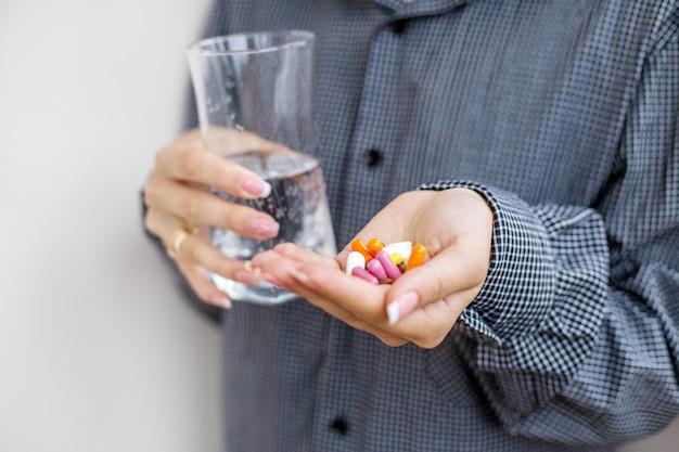 あなたの手の中に丸薬とビタミンとコップ一杯の水。