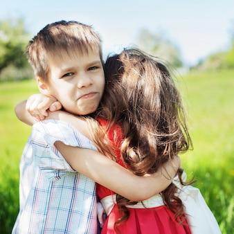 小さな男の子が彼の妹を抱いています。