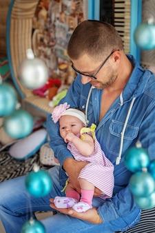 幼児が両腕に抱いている若い父親。
