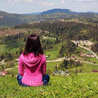 若い女性が地面に座って山を見ています。