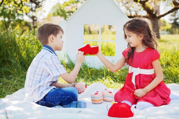 ピクニックティーに幸せな子供たち。幼年期および生活様式の概念。