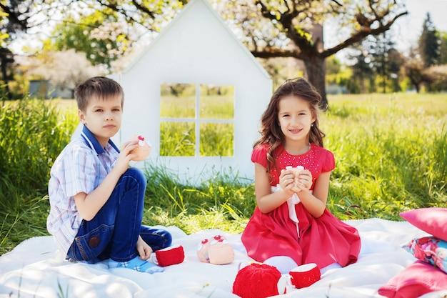 緑豊かな庭園でピクニックに子供たち。幼年期および生活様式の概念。