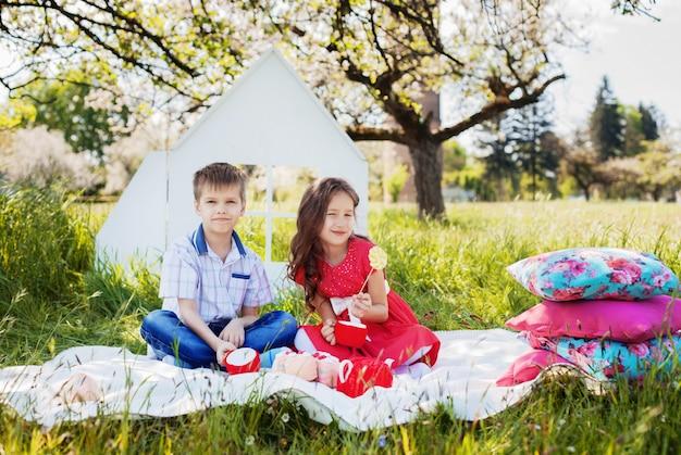 スタイリッシュな小さな男の子とピクニックに美しい巻き毛の女の子。幼年期および生活様式の概念。