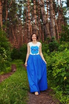 面白い女性が森を歩いています。夏。ライフスタイル、自然、旅行の概念