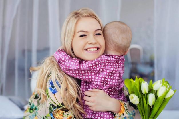 小さな子供がお母さんを抱きしめて花をあげる。幼年期、教育、家族の概念