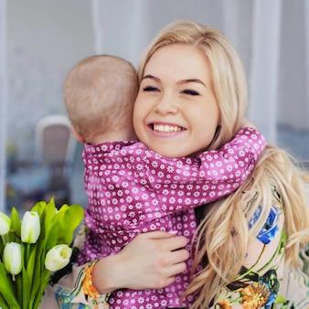 小さな子供がお母さんを抱きしめて花をあげる。幼年期、教育、家族の概念。