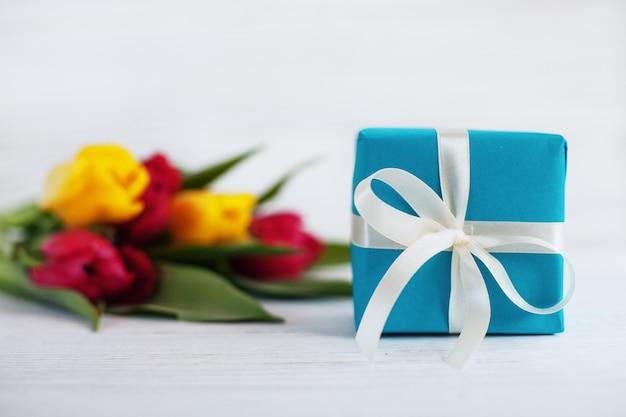 Белые деревянные фон тюльпаны и подарок. концепция праздника, бир